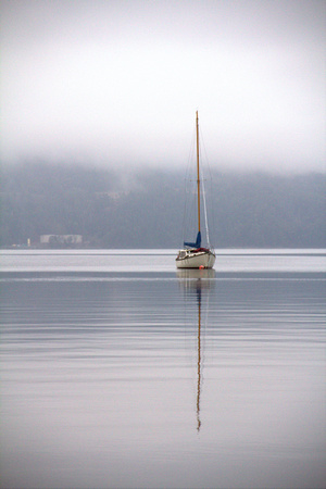 lone sailboat anchored adrift bay blue vancouver island yacht moored fog grey water